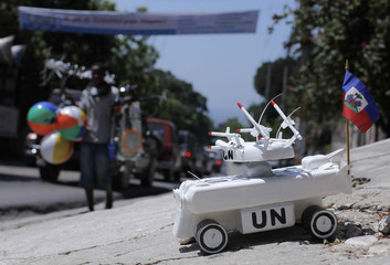 A toy U.N. tank, made from recycled plastic bottles and selling for $20, is displayed on a street in Port-au-Prince