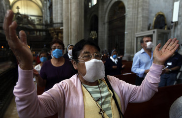 People wear masks as they attend a mass in Mexico City's Metropolitan Cathedral