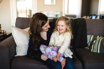 Woman sitting on sofa with daughter on knee