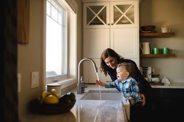 Mother helping toddler son wash hands at kitchen sink