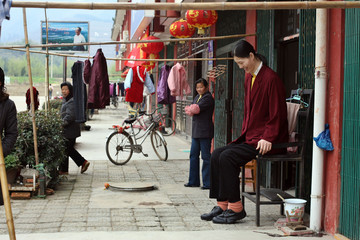 The tallest woman in Asia, Chinese Yao Defen (R), sits at the entrance of her home in Shu Cha in eas..