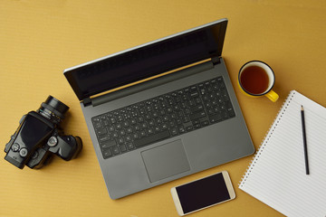 High resolution image of laptop,camera,smart phone and notepad with pencil and coffee on brown background,