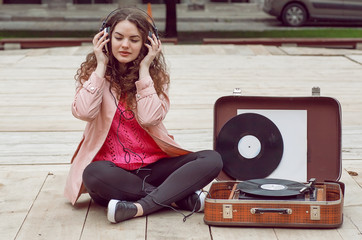 Beautiful hipster girl with old vintage vinyl records. Listen to music with emotions