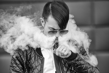 Vape man. Portrait of a handsome young white guy with modern haircut in aviator sunglasses vaping and letting off steam from an electronic cigarette. Black and white photo. Lifestyle.