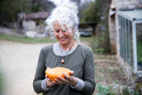 Mature female gardener holding squash vegetable in garden