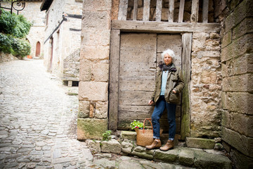 Woman leaning against wooden door, Bruniquel, France