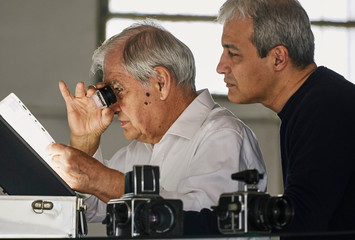 Father and son looking at sheet of film slides