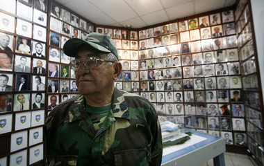Member of Brigade 2506 stands in front of pictures of deceased comrades during a ceremony to honor opponents of the Castro government, in Miami, Florida