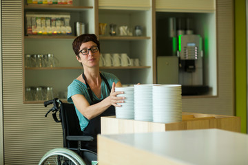 Woman in wheelchair, working in restaurant, stacking bowls