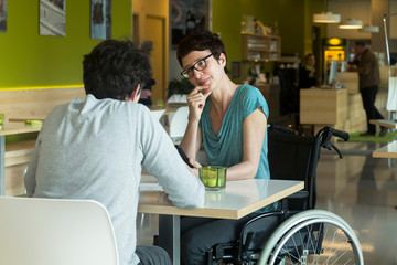 Woman in wheelchair, sitting at restaurant table with friend