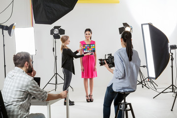 Photographer checking colour setting in white backdrop photography studio shoot