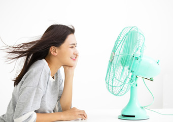 smiling woman cooling herself by electric fan