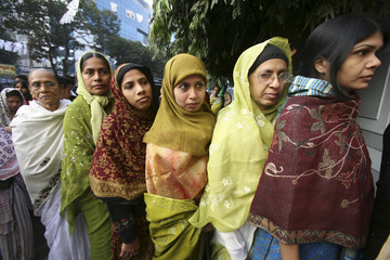 Women queue to cast their votes at a polling booth in Dhaka