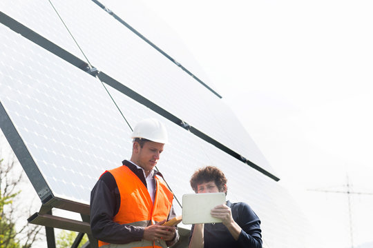Male and female engineers looking at digital tablet on solar panel site