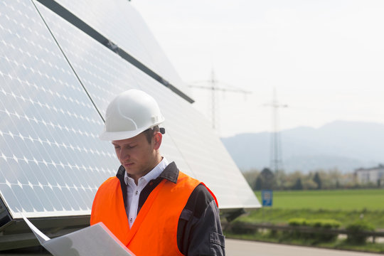 Male engineer looking at paperwork on solar panel site