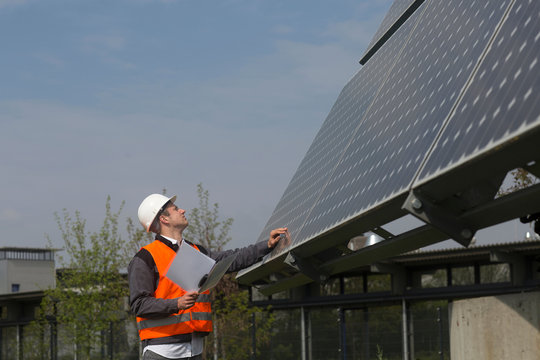 Young male engineer using digital tablet looking up at solar panels