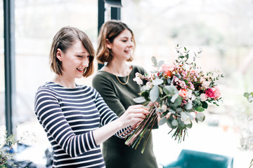 Florist students arranging bouquets at flower arranging workshop