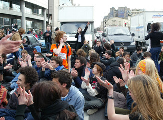 Students clap hands as they block traffic during a protest against the youth job law in Paris