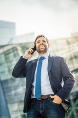 Happy businessman making smartphone call in city