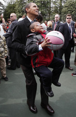 U.S. President Barack Obama picks up a boy to help him shoot a basketball as part of the Annual Easter Egg Roll on the South Lawn at the White House in Washington