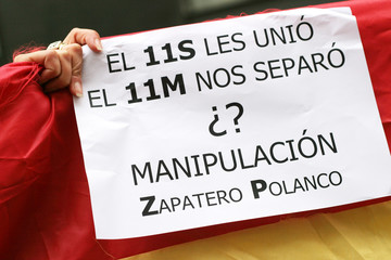 Demonstrators hold a Spanish flag as Spanish PM Zapatero testifies before a parliamentary commission ...