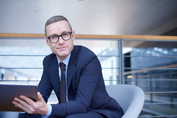 Portrait of confident businessman holding laptop on office balcony