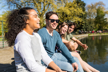Four young adult friends sitting on lakeside in Battersea Park