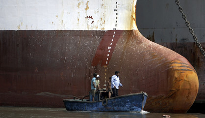 People in a boat go past a ship at a dockyard in an industrial area in Mumbai