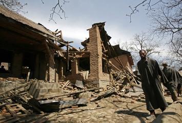 Kashmiri Muslim villagers walk past the debris of a residential house after a gun battle in Machoowara