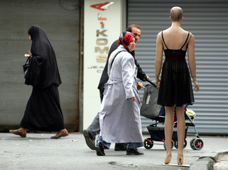 A couple walks past a mannequin displaying lingerie outside a shop in downtown Istanbul