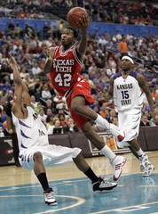 Red Raiders Burgess drives past Wildcats Young and Hoskins in Oklahoma City