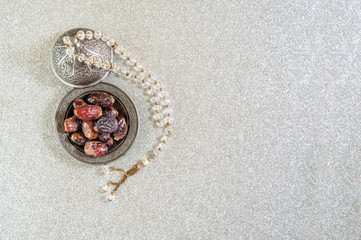 Islam kurma, ramadan, date palm fruits on a metal tray placed on a glitter sparkle background.