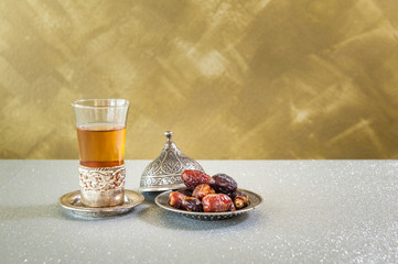 Islam kurma, ramadan, date palm fruits and Tea on a metal tray placed on a glitter sparkle background.