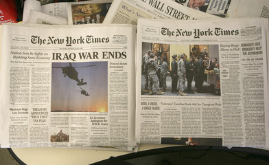 "A fake copy of the New York Times declaring ""Iraq War Ends"" is seen here with a copy of the real New York Times"
