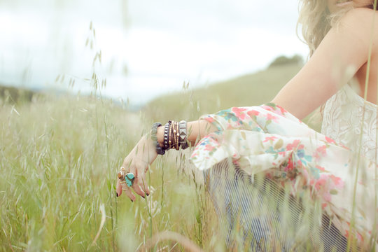 Cropped shot of boho woman wearing bangles and rings sitting in field of long grass