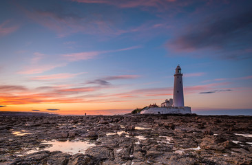 Foto op Canvas Vuurtoren Dusk at St Mary's Lighthouse / St Mary's Lighthouse on a small rocky Island, just north of Whitley Bay on the North East coast of England. A causeway submerged at high tide links to the mainland