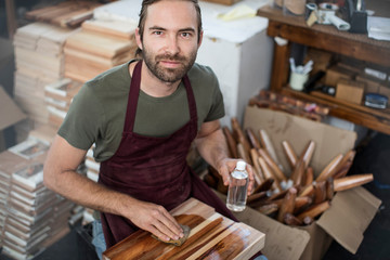 Portrait of man applying wood stain to chopping board in factory