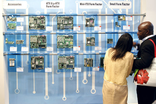 Visitors chat next to a display of DFI's computer motherboards, during the first day of the Computex trade show in Taipei
