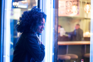 Woman looking through cafe window at night