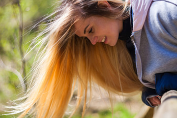 Young woman with long blond hair during walk in park