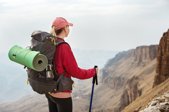 A slender girl in a cap with sticks for Nordic walking with a backpack and a folded rug for relaxation stands in the mountains against the backdrop of rocks and distant lands