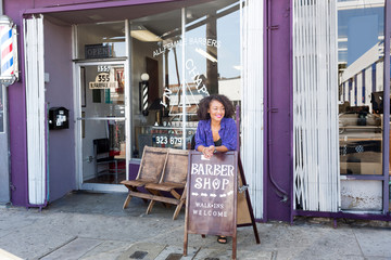 Female barber outside barber shop front