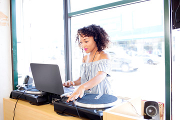 Female disc jockey playing turntable and laptop music in barber shop