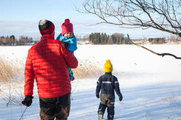 Father and two sons walking in snow covered landscape, rear view