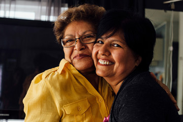 Portrait of mother and adult daughter hugging