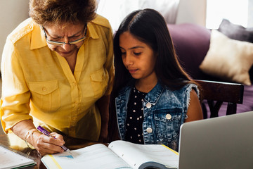 Grandmother helping granddaughter with homework