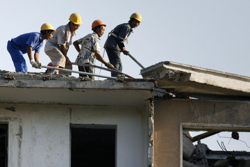 Workers demolish old residential building for construction of new commercial structure in Beijing