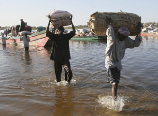 Traders carry goods from a pirogue coming from Nigeria in Bol Chad