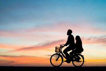 Silhouette couple and bycicle on sunset.