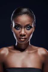 Beauty portrait of African American woman looking straight into the camera. Studio portrait on dark background